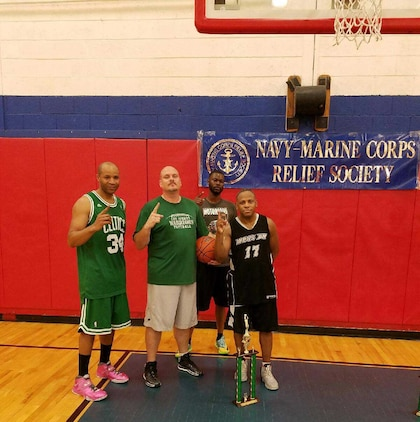 """Maj. Lee Taylor (right), and teammates (left to right) Gunnery Sgt. Jerome McCray, Stewart Snoddy and Tennoris Knox walk away with the 1st place trophy in a 3-on-3 basketball tournament at Marine Corps Logistics Base Albany's Thomason Gym, recently. """"We went undefeated throughout the tournament and played a total of four games,"""" Taylor said on his team's championship win. Eight teams participated in the event, which was one of three activities held on the installation to raise money during the Navy-Marine Corps Relief Society's Fund Drive."""