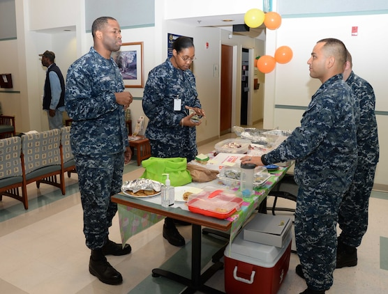 Petty Officer 1st Class Antresha Holmes (center) purchases items from a desserts table during a Navy-Marine Corps Relief Society's Fund Drive bake sale, as Petty Officer 1st Class Kishaun Jeffers (left) looks on. The event, which was held at Naval Branch Health Clinic-Albany, aboard Marine Corps Logistics Base Albany, recently, was the final of three activities organized to raise money to assist military families in their time of unexpected, temporary crises. Petty Officer 3rd Class Louis Amaya Sanchez (right), laboratory technician, NBHC-Albany, is the clinic's NMCRS representative/point of contact.