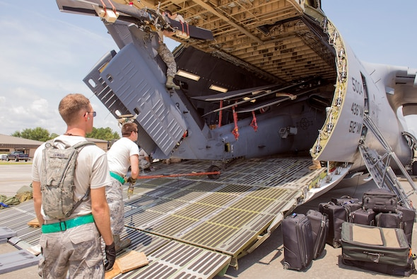 U.S. Air Force Airmen from the 723d Aircraft Maintenance Squadron load an HH-60G Pave Hawk onto a HC-130J Combat King II outside of the Deployment Control Center prior to deploying, July 16, 2015, at Moody Air Force Base, Ga. The DCC prepares, evaluates and supervises all logistical operations to determine deployment tasking for Moody's personnel. (U.S. Air Force photo by Airman 1st Class Greg Nash/Released)