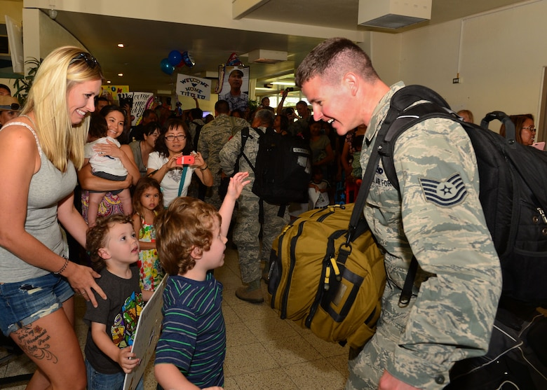 A Tech. Sgt. from the 154th Aircraft Maintenance Squadron greets his family after returning from a six-month deployment , on Joint Base Pearl Harbor-Hickam, , April 5, 2016.(U.S. Air Force photo by Tech. Sgt. Aaron Oelrich/released)