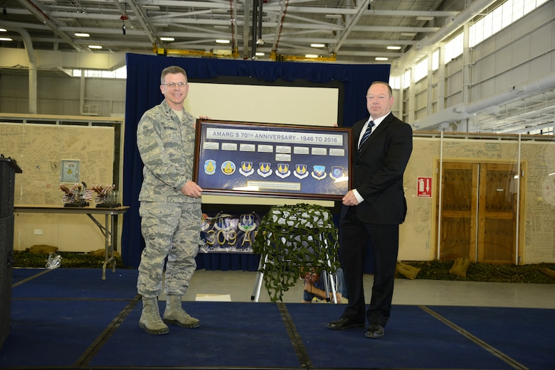 U.S. Air Force Brig. Gen. Steven J. Bleymaier, Commander of Ogden Air Logistics Complex at Hill Air Force Base, Utah, presents a commemorative plaque to Tim Gray, 309th Aerospace Maintenance and Regeneration Group deputy director, during the 70th Anniversary Celebration of the 309th AMARG at Davis-Monthan Air Force Base, Ariz., April 4, 2016.  Although the name has changed over the years the organization has continued achieving its mission elements: aircraft storage and preservation, reclaiming and returning vital parts into the supply chain, regenerating valuable aircraft to flying service and providing limited depot maintenance and modifications.  (U.S. Air Force Photo by Senior Airman Chris Massey/Released)