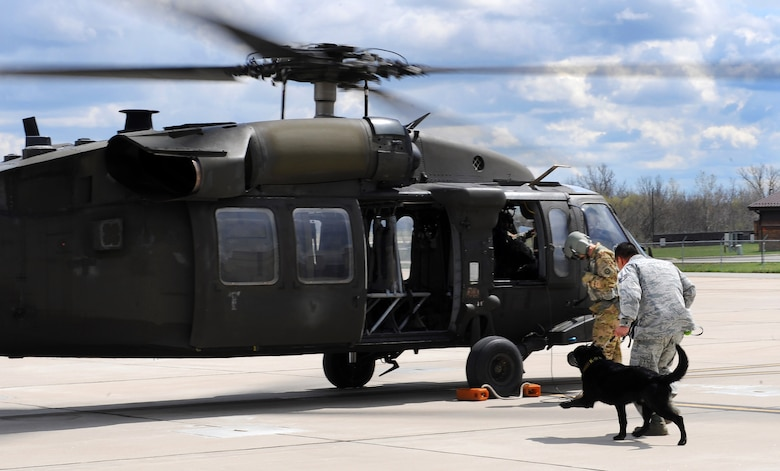 U.S. Air Force Staff Sgt. Ki Seung Nam, a 509th Security Forces Squadron military working dog (MWD) handler, runs toward a UH-60 Black Hawk helicopter with MWD Buda for an orientation flight at Whiteman Air Force Base, Mo., April 1, 2016. The 1-135th Attack Reconnaissance Battalion trains with the 509th Security Forces Squadron's MWDs and their handlers for search and rescue or other operations that would require the MWDs to be air lifted. (U.S. Air Force photo by Airman 1st Class Michaela R. Slanchik)