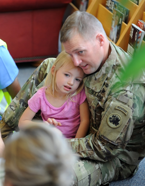 Capt. Chris Pulliam, 121st Infantry, Company H commander, and his daughter Morgan Pulliam, 3, enjoy a story time book reading at the base library.  Month of the Military Child story time will be held April 13 at 10 a.m. (U.S. Air Force photo by Tommie Horton)