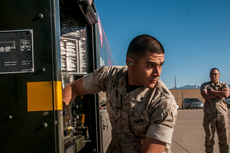 Marine Corps Lance Cpl. Alejandro Chiquette, a bulk fuel specialist from Bulk Fuel Company Alpha, 6th Engineer Support Battalion, practices tending to the pumping system on a truck engine, which eventually transfers the fuel to a jet.  Beginning in late March and ending in early June, the Marines will be training and executing operational tasks at the 162nd Wing.  (U.S Air National Guard Photo by Tech. Sgt. Erich B. Smith/Released)