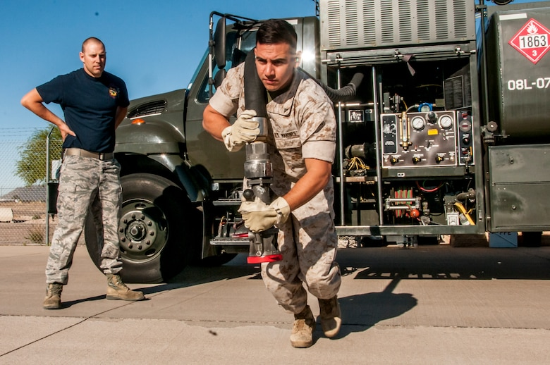 TUCSON, Ariz. -- Under the watchful eye of Air Force Staff Sgt. Scott Frank, Marine Corps Lance Cpl. Paul Robledogarcia, a bulk fuel specialist from Bulk Fuel Company Alpha, 6th Engineer Support Battalion – home-based out of Davis-Monthan Air Force Base, practices pulling a fuel hose out of a tanker. Franks said that eventually fuels specialist would hand the nozzle to a crew chief, later ensuring that a proper connection to the aircraft is made, eliminating the possibility of fuel leaks. Beginning in late March and ending in early June, the Marines will be training and executing operational tasks at the 162nd Wing. (U.S Air National Guard Photo by Tech. Sgt. Erich B. Smith)
