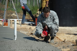 Capt. Joseph Miller, 820th RED HORSE Squadron, quality control officer in charge, checks the consistency of the concrete while local Dominican contractors create a foundation for a new clinic in Copeyito, Dominican Republic as part of Exercise NEW HORIZONS 2016, Apr. 8, 2016. Members of the 820th RED HORSE Squadron, from Nellis Air Force Base, Nevada, provide Quality Control and Quality Assurance during the foundation preparation. (U.S. Air Force photo by Master Sgt. Chenzira Mallory/Released)