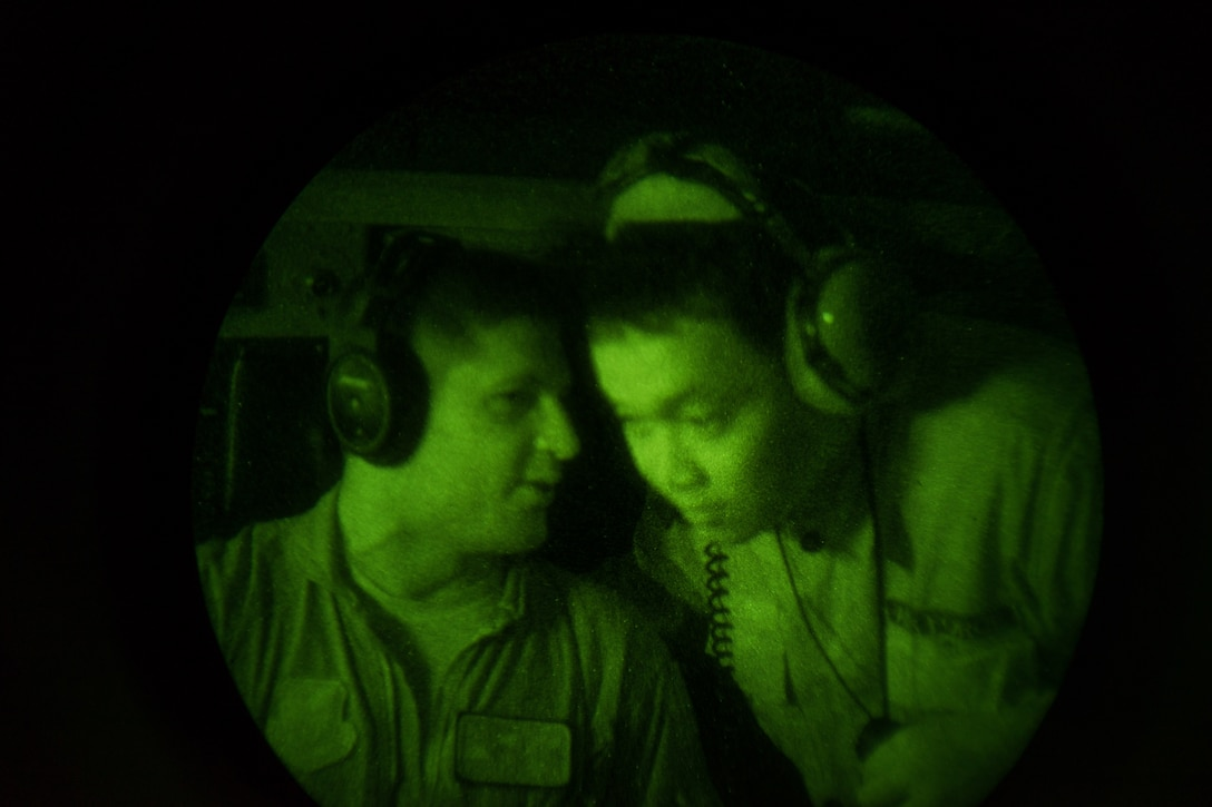 U.S. Air Force Capt. Andrew Kochman, 36th Airlift Squadron C-130 Hercules aircraft navigator, talks to a Philippine Air Force member from the 220th Airlift Wing April 7, 2016, during an Exercise Balikatan 2016 night flight over the Philippine Islands. PAF pilots and aircrew do not currently have night vision goggle capabilities, so the training given to them from members of the 36th AS was an entirely new experience. U.S. and Philippine military forces continually modernize and develop partner capabilities through bilateral exercises and subject matter expert exchanges. (U.S. Air Force photo by Staff Sgt. Michael Smith/Released)