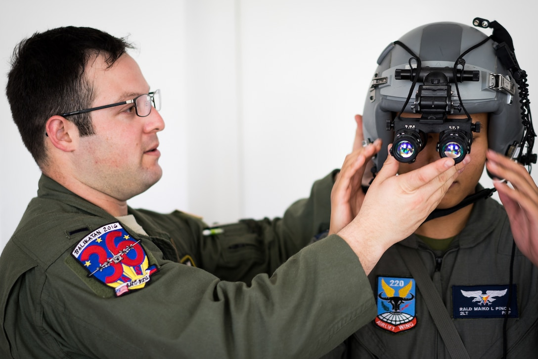 U.S. Air Force 1st Lt. Scott Brooks, 36th Airlift Squadron C-130 Hercules aircraft pilot, helps Philippine Air Force 2nd Lt. Rald Pinca, 220th Airlift Wing pilot, try on a flight helmet  April 7, 2016, during an Exercise Balikatan 2016 training session on Mactan-Benito Ebuen Air Base, Philippines. Pilots and loadmasters from the 36th AS shared their experiences of using night vision goggles and night flying during an all-day training session. BK16 provides opportunities for U.S. and Philippine forces to come together and train for potential real world events and crises. (U.S. Air Force photo by Staff Sgt. Michael Smith/Released)
