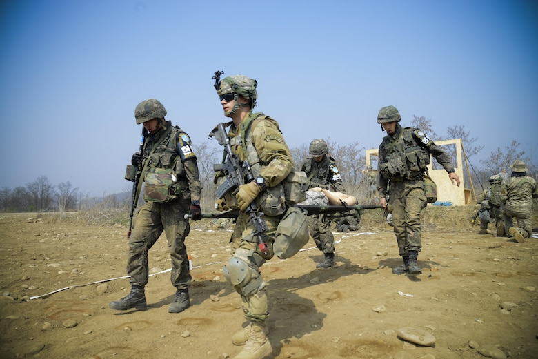 Republic of Korea and U.S. Army Joint Security Area Security Battalion fire team members four-man carry a simulated injured service member during a joint search and recovery exercise April 8, 2016, at Camp Bonifas, Republic of Korea. 51st Civil Engineer Squadron fire prevention firefighters assisted in the exercise by teaching ROK and U.S. Soldiers how to safely enter a crashed aircraft to rescue individuals. (U.S. Air Force photo by Senior Airman Dillian Bamman/Released)