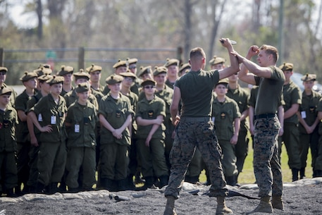 U.S. Navy Petty Officer 3rd Class Christopher Marlo, a hospital corpsman and black belt Martial Arts Instructor with 2nd Medical Battalion (right), breaks down the movements used to counter a knife attack at Camp Lejeune, N.C., March 16, 2016. A total of 46 cadets with the Argyll and Sutherland Highlanders of Canada Regimental Cadet Corps visited the base and multiple units as part of an educational tour to better understand how foreign militaries function.