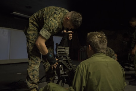 Lance Cpl. Luke Dailey, an indoor simulated marksmanship trainer with the Battle Skills Training School, operated by the 2nd Marine Logistics Group, teaches a Canadian cadet how to load a MK19 40mm grenade launcher at Camp Lejeune, N.C., March 15, 2016. A total of 46 cadets with the Argyll and Sutherland Highlanders of Canada Regimental Cadet Corps visited the base and multiple units as part of an educational tour to better understand of how foreign militaries function. (U.S. Marine Corps photo by Lance Cpl. Preston McDonald/Released)