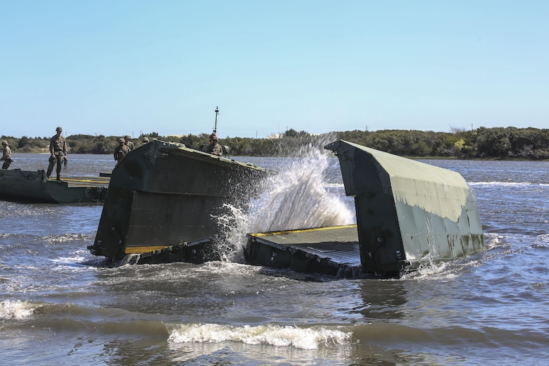A water bay dropped by Marines with Bridge Company, 8th Engineer Support Battalion unfolds upon impact during the set-up of a water-crossing bridge as part of exercise Saipan Rain at Camp Lejeune, N.C., March 30, 2016. The Marines constructed the bridge to allow Marines, vehicles, and equipment, with 10th and 14th Marine Regiments to conduct a water gap crossing. (U.S. Marine Corps photo by Cpl. Paul S. Martinez/Released)