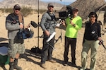 """Nutan Chada (right), executive producer of the DLA Video Production Team, leads a contract crew on the """"set"""" of Exercise Steel Knight, Twentynine Palms, California, for a Logistics On Location video December 2015."""
