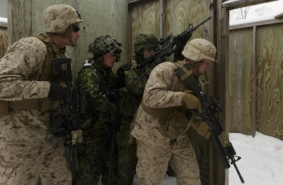 Cpl. Joseph A. Childs (right), a team leader with 1st Platoon, Company I, 3rd Battalion, 25th Marine Regiment, 4th Marine Division, Marine Forces Reserve, leads a fire team of Marines and soldiers from the Danish Home Guard through a room clearing drill during exercise Arctic Eagle at Camp Grayling, Mich., April 6, 2016. The Marines joined soldiers with the U.S. Army National Guard and the Danish Home Guard in the bilateral exercise, designed to simulate a joint task force defending key infrastructure in the arctic region. (U.S. Marine Corps photo by Cpl. Ian Leones/Released)