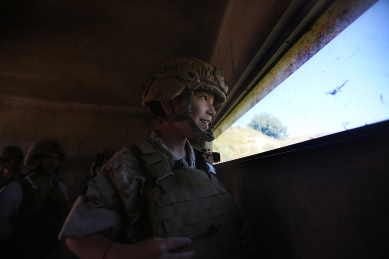 Nathan Aldaco, a 12 year-old boy with hypoplastic left heart syndrome, looks out of a bunker during a Make-A-Wish event supported by 7th Engineer Support Battalion, 1st Marine Logistics Group, aboard Camp Pendleton, Calif., March 24, 2016. Marines with 7th ESB and Explosive Ordnance Disposal helped to make Nathan's wish of becoming a Marine come true by demonstrating the capabilities of their EOD robots and detonating TNT, C4, dynamite and blasting caps, while the heavy equipment operators gave him the opportunity to ride the D7 dozer and the excavator, in which he dug a pit, built a berm, and broke several large tree trunks.  (U.S. Marine Corps photo by Sgt. Laura Gauna/released)