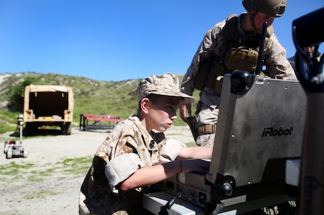 Nathan Aldaco, a 12 year-old boy with hypoplastic left heart syndrome, controls a Pacbot during a Make-A-Wish event supported by 7th Engineer Support Battalion, 1st Marine Logistics Group, aboard Camp Pendleton, Calif., March 24, 2016. Marines with 7th ESB and Explosive Ordnance Disposal helped to make Nathan's wish of becoming a Marine come true by demonstrating the capabilities of their EOD robots and detonating TNT, C4, dynamite and blasting caps, while the heavy equipment operators gave him the opportunity to ride the D7 dozer and the excavator, in which he dug a pit, built a berm, and broke several large tree trunks.  (U.S. Marine Corps photo by Sgt. Laura Gauna/released)