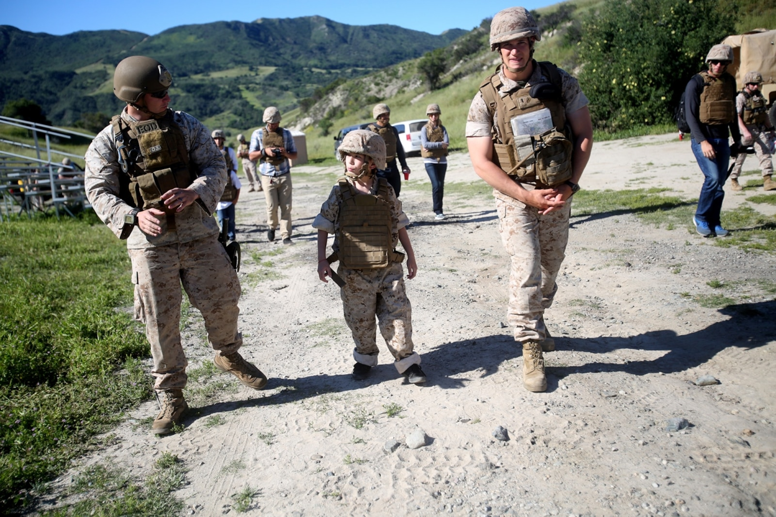 Nathan Aldaco, a 12 year-old boy with hypoplastic left heart syndrome, walks with Marines to a demolition site during a Make-A-Wish event supported by 7th Engineer Support Battalion, 1st Marine Logistics Group, aboard Camp Pendleton, Calif., March 24, 2016. Marines with 7th ESB and Explosive Ordnance Disposal helped to make Nathan's wish of becoming a Marine come true by demonstrating the capabilities of their EOD robots and detonating TNT, C4, dynamite and blasting caps, while the heavy equipment operators gave him the opportunity to ride the D7 dozer and the excavator, in which he dug a pit, built a berm, and broke several large tree trunks.  (U.S. Marine Corps photo by Sgt. Laura Gauna/released)