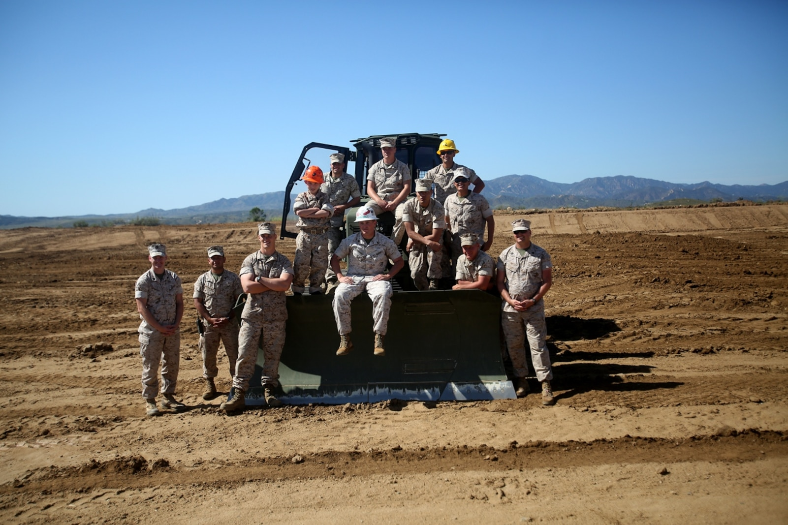 Nathan Aldaco, a 12 year-old boy with hypoplastic left heart syndrome, poses for a photo with heavy equipment operators during a Make-A-Wish event supported by 7th Engineer Support Battalion, 1st Marine Logistics Group, aboard Camp Pendleton, Calif., March 24, 2016. Marines with 7th ESB and Explosive Ordnance Disposal helped to make Nathan's wish of becoming a Marine come true by demonstrating the capabilities of their EOD robots and detonating TNT, C4, dynamite and blasting caps, while the heavy equipment operators gave him the opportunity to ride the D7 dozer and the excavator, in which he dug a pit, built a berm, and broke several large tree trunks.  (U.S. Marine Corps photo by Sgt. Laura Gauna/released)