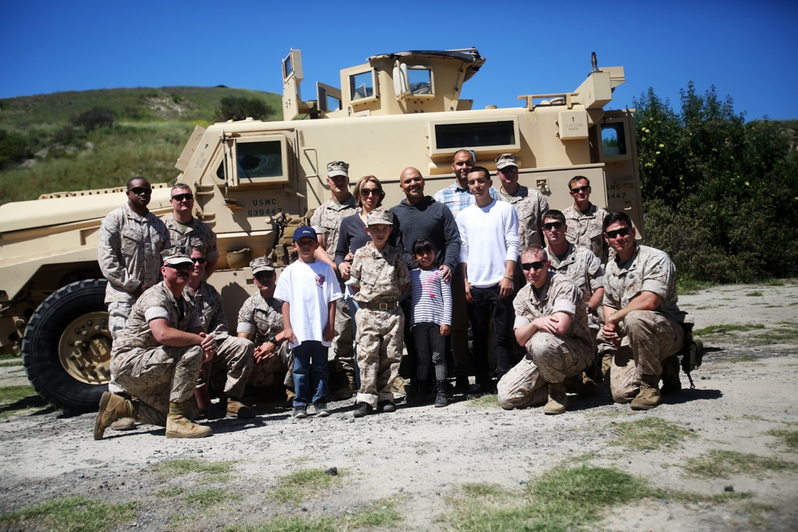 Nathan Aldaco, a 12 year-old boy with hypoplastic left heart syndrome, and his family, pose for a picture with Explosive Ordnance Disposal Marines during a Make-A-Wish event supported by 7th Engineer Support Battalion, 1st Marine Logistics Group, aboard Camp Pendleton, Calif., March 24, 2016. Marines with 7th ESB and Explosive Ordnance Disposal helped to make Nathan's wish of becoming a Marine come true by demonstrating the capabilities of their EOD robots and detonating TNT, C4, dynamite and blasting caps, while the heavy equipment operators gave him the opportunity to ride the D7 dozer and the excavator, in which he dug a pit, built a berm, and broke several large tree trunks. (U.S. Marine Corps photo by Sgt. Laura Gauna/released)
