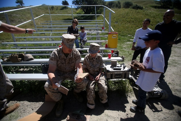 Nathan Aldaco, a 12 year-old boy with hypoplastic left heart syndrome, prepares to eat field rations with 1st Lt. Ernest Gaudio during a Make-A-Wish event supported by 7th Engineer Support Battalion, 1st Marine Logistics Group, aboard Camp Pendleton, Calif., March 24, 2016. Gaudio is a platoon commander with Bravo Company, 7th ESB, 1st MLG. Marines with 7th ESB and Explosive Ordnance Disposal helped to make Nathan's wish of becoming a Marine come true by demonstrating the capabilities of their EOD robots and detonating TNT, C4, dynamite and blasting caps, while the heavy equipment operators gave him the opportunity to ride the D7 dozer and the excavator, in which he dug a pit, built a berm, and broke several large tree trunks.  (U.S. Marine Corps photo by Sgt. Laura Gauna/released)