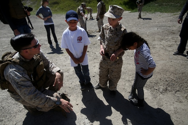 Nathan Aldaco, a 12 year-old boy with hypoplastic left heart syndrome, along with his brother and sister learn about TNT during a Make-A-Wish event supported by 7th Engineer Support Battalion, 1st Marine Logistics Group, aboard Camp Pendleton, Calif., March 24, 2016. Marines with 7th ESB and Explosive Ordnance Disposal helped to make Nathan's wish of becoming a Marine come true by demonstrating the capabilities of their EOD robots and detonating TNT, C4, dynamite and blasting caps, while the heavy equipment operators gave him the opportunity to ride the D7 dozer and the excavator, in which he dug a pit, built a berm, and broke several large tree trunks.  (U.S. Marine Corps photo by Sgt. Laura Gauna/released)