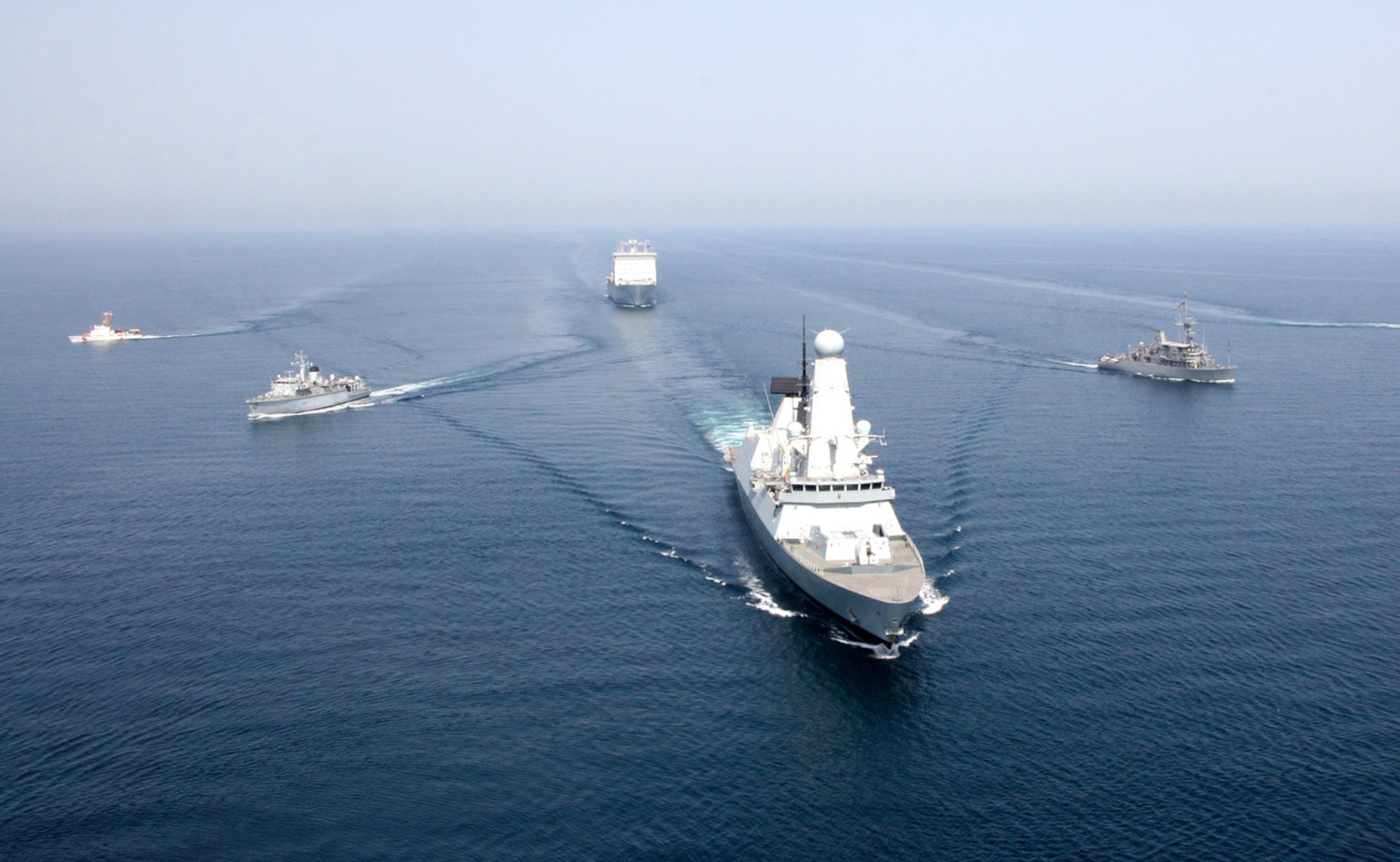 Royal Navy ship HMS Defender and Royal Fleet Auxiliary ship RFA Cardigan Bay anchor a formation of coalition mine countermeasures and maritime security vessels at sea, operating in support of the International Mine Countermeasures Exercise (IMCMEX). IMCMEX includes navies from more than 30 countries spanning six continents training together across the Middle East. (Royal Navy photo)