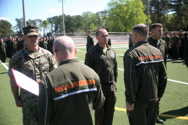 """Sgt. Benjamin D. Patrick (center), a scout with 2nd Light Armored Reconnaissance Battalion, stands at attention as his Navy and Marine Corps Achievement Medal Citation is read aloud at Camp Lejeune, N.C., April 8, 2016. Patrick won the competition and was awarded the Navy and Marine Corps Achievement Medal, a four-day weekend, and the title """"2nd LAR's Best Scout."""" (U.S. Marine Corps photo by Cpl. Joey Mendez)"""