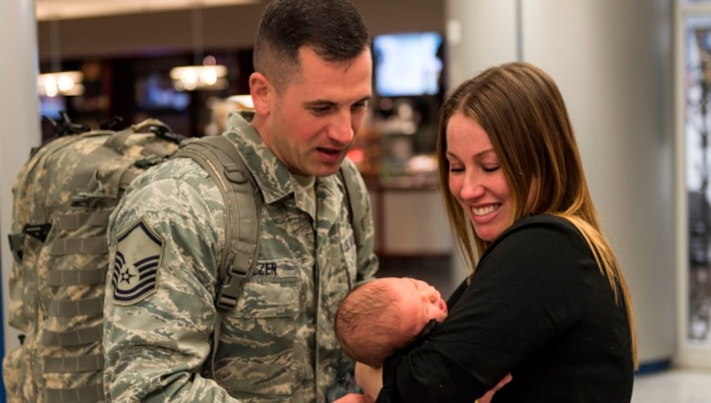 Master Sgt. Joseph Molzen, an Airman assigned to the 107th Security Forces Squadron, Niagara Falls Air Reserve Station, N.Y. gets to see his newborn daughter for the first time. Molzen was one of more than 30 Airmen from the 107th SFS to return from a six-month deployment to Southwest Asia, Feb. 4-5, 2016. (U.S. Air National Guard photo by Staff Sgt. Ryan Campbell/Released)