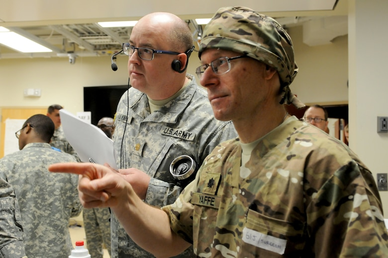 U.S. Army Reserve Maj. John Laymon (left) observes as Lt. Col. Michael Yaffe (right), a trauma surgeon with the 399th Combat Support Hospital, 804th Medical Brigade, 3d Medical Command (Deployment Support), gives direction and receives feedback from his team April 2, 2016 during an exercise at the Mayo Clinic Multidisciplinary Simulation Center in Rochester, Minnesota. Laymon, a nurse practitioner with the 4224th U.S. Army Hospital, Central Medical Area Readiness Support Group, Army Reserve Medical Command, Des Moines, Indiana, served as an observer-controller/trainer during the exercise, which focused on helping the unit implement the Team Strategies and Tools to Enhance Performance and Patient Safety, or TeamSTEPPS, framework.