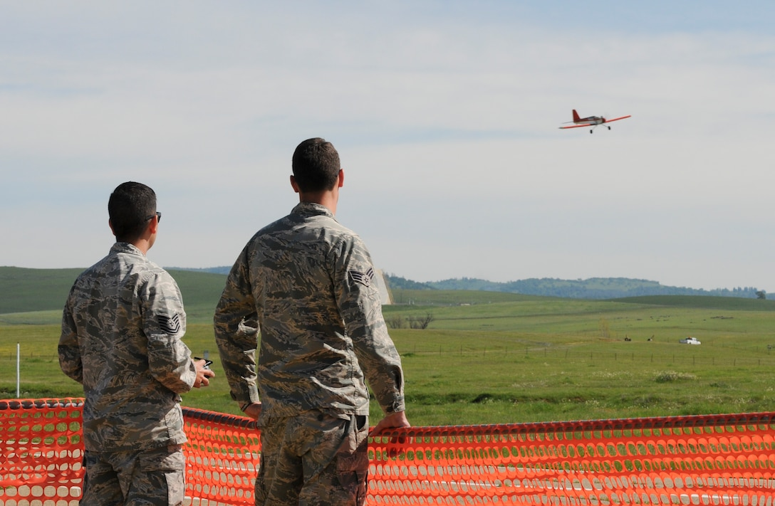 Tech. Sgt. Michael Carrillo (left), 349th Air Mobility Wing Detachment 1 KC-135 crew chief, flies a radio-controlled aircraft as an Airman observes at Beale Air Force Base, California March 25, 2016. Carrillo has been a member of the Beale Blackbirds Radio Control Club for more than six months. (U.S. Air Force photo by Senior Airman Michael J. Hunsaker)