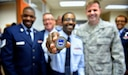 Senior Airman Vincent Lang, 932nd Medical Squadron public health technician, is presented with a chief's coin from newly appointed 932nd Airlift Wing command chief, Chief Master Sgt. Chad Welch, during a surprise gathering by fellow MDS Airmen April 3, 2016, Scott Air Force Base, Illinois.  Lang was recognized for his job performance, can do attitude and volunteer efforts within the Wing.  (U.S. Air Force photo by Tech. Sgt. Christopher Parr)
