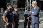 U.S. Secretary of State John Kerry chats with a group of New York City police officers before making his way to the United Nations Headquarters to hear President Obama address the General Assembly on September 24, 2014. [State Department photo/ Public Domain]