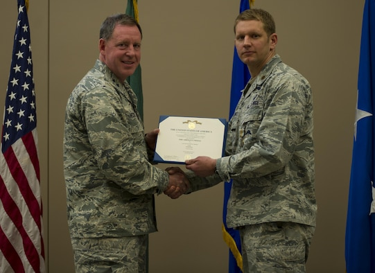 Maj. Matthew Arnold, right, the 336th Training Group chief of standards and evaluations, receives the Airman's Medal during a ceremony April 8, 2016, at Fairchild Air Force Base, Wash. In 2013, Arnold and Tech. Sgt. Dean Criswell, the 22nd Special Tactics Squadron NCO in charge of rescue operations, were participating in a routine training exercise in Okinawa, Japan, when an HH-60G Pave Hawk went down. They helped save three of the four Airmen on the helicopter. (U.S. Air Force photo/Airman 1st Class Sean Campbell)