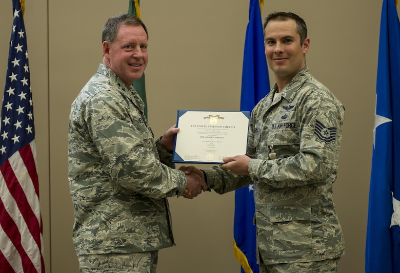 Tech. Sgt. Dean Criswell, right, the 22nd Special Tactics Squadron NCO in charge of rescue operations, receives the Airman's medal during a ceremony April 8, 2016, at Fairchild Air Force Base, Wash. Criswell and Maj. Matthew Arnold, the 336th Training Group chief of standards and evaluations, put their lives in danger to save the lives of three Airmen on a HH-60G Pave Hawk that crashed during training. (U.S. Air Force photo/Airman 1st Class Sean Campbell)