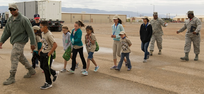 An Airman from Holloman's Basic Expeditionary Airfield Resources (BEAR) Base leads a group of children to the next station during Operation K.I.D. (Kids Investigating Deployment), April 8 at Holloman Air Force Base, N.M. April is the Month of the Military Child. The Airmen and Family Readiness Center and Youth Center hosted Operation K.I.D. to expose military children to the different phases of deployment that their active duty family members go through.