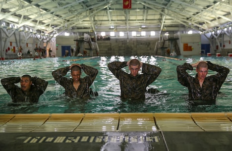 Recruits of Lima Company, 3rd Recruit Training Battalion, hold their hands about their heads after finishing the 10-second gear strip during the Water Survival Basic Qualification at Marine Corps Recruit Depot San Diego, April 11. This qualification will be valid for the recruits for two years. Depending on their military occupational specialty, they may go through higher qualification levels. Annually, more than 17,000 males recruited from the Western Recruiting Region are trained at MCRD San Diego. Lima Company is scheduled to graduate June 10.
