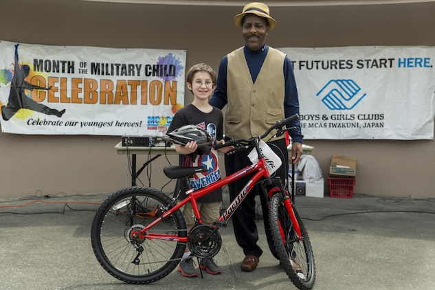 Adam Boardman, a third grader at Matthew C. Perry Elementary School, poses for a photo with Eugene Clark, Youth and Teen Center director, after winning a bike in a raffle during the 13th annual Month of the Military Child festival at Marine Corps Air Station Iwakuni, Japan, April 9, 2016. The month of April honors and recognizes military children for the struggles they overcome such as frequent moves, school changes and separation from active duty parents. (U.S. Marine Corps photo by Lance Cpl. Aaron Henson/Released)