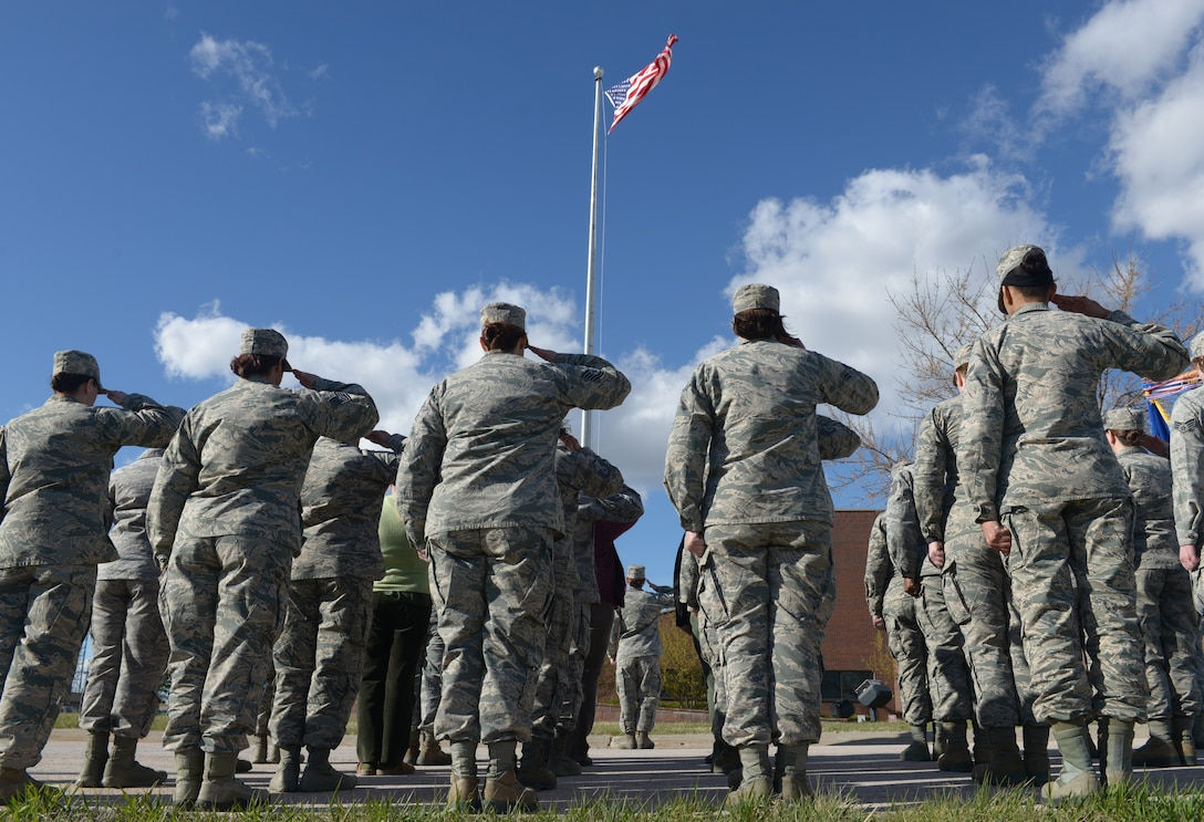 Airmen salute the American flag as it is lowered during the women's retreat ceremony at Ellsworth Air Force Base, S.D., April 7, 2016. A formation of female Airmen for retreat was coordinated to honor women in public service and government in recognition of Women's History Month. (U.S. Air Force photo by Airman Donald C. Knechtel/Released)