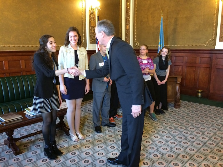 Ria Gualano, daughter of Lan Gualano, 28th Comptroller Squadron quality assurance manager, shakes hands with Dennis Daugaard, South Dakota governor, at Box Elder, S.D., March 21, 2016. The Military Youth of the Year competition is a part of Boys & Girls Clubs of the America's premier youth recognition program for members who promote service to the Club, community, and family; as well as good academic performance, moral character, life goals, poise and public speaking ability. (Courtesy photo by Lan Gualano/Released)