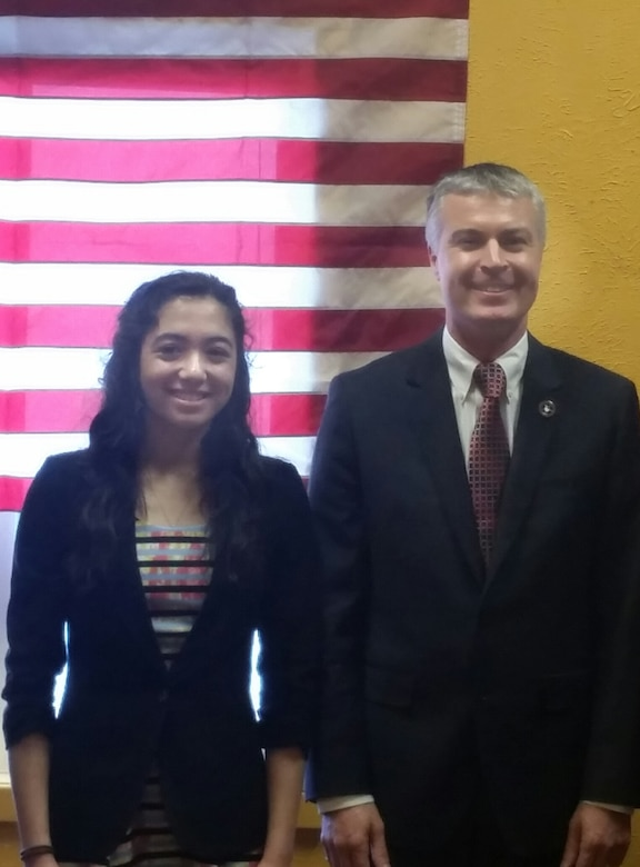 Ria Gualano, daughter of Lan Gualano, 28th Comptroller Squadron quality assurance manager, is commemorated by Marty Jackley, South Dakota Attorney General, for being selected as South Dakota's Military Youth of the Year, at Box Elder, S.D., March 21, 2016. For the competition, applicants had to write four essays covering different areas in teen life and their vision for the youth in America. (Courtesy photo by Lan Gualano/Released)