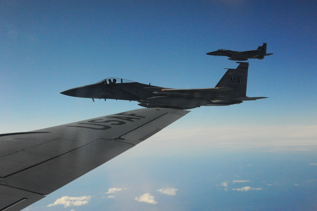 Two U.S. Air Force F-15C Eagle fighter aircraft assigned to the 104th Fighter Wing, Barnes Air National Guard Base, Mass., fly alongside a U.S. Air Force KC-135 Stratotanker from the 916th Air Refueling Wing, Air Force Reserve Command, Seymour Johnson, N.C. after taking fuel in the skies over Iceland while conducting Air Surveillance operations. Deterrence missions such as this communicates that the U.S. is serious about security and stability in the region. (U.S. Air Force photo by Master Sgt. Kevin Nichols/Released)