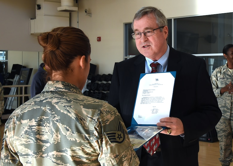 Thomas Fitzgerald, Space and Missile Systems Center acting executive director, presents a certificate and letter of selection for Officer Training School through the Senior Leader Enlisted Commissioning Program from Gen. John Hyten, commander of Air Force Space Command to Staff Sgt. Katelin Robinson, 61st Medical Squadron noncommissioned officer in charge of Dental Logistics at the Los Angeles Air Force Base medical clinic in El Segundo, Calif. (U.S. Air Force photo/Sarah Corrice)