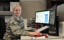Senior Airman Kelsey Janckila poses for a photo at her desk at the 148th Fighter Wing April 10, 2016.  Janckila, a member of the logistics squadron command support staff, plans to graduate in the fall of 2016 with a degree in communications.  (U.S. Air National Guard Photo by Tech. Sgt. Scott G. Herrington/Released)