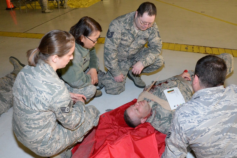 U.S. Air Force Airmen with the Indiana Air National Guard, 181st Intelligence Wing tend to a fellow Airman's injury during an exercise at Hulman Field Air National Guard base, Ind., April 9, 2016. The exercise simulated an F-1 tornado passing through the base causing destruction to buildings and how the wing would respond. (U.S. Air National Guard photo by Senior Airman Lonnie Wiram)