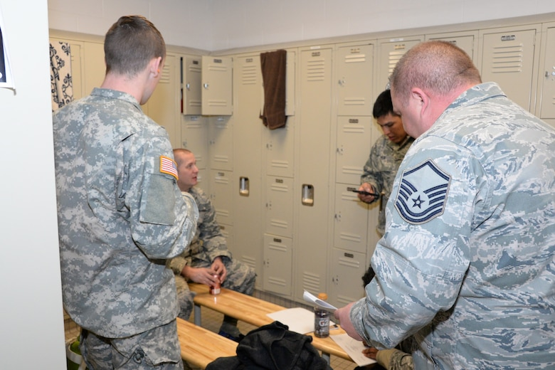 U.S. Air Force Airmen with the Indiana Air National Guard, 181st Intelligence Wing, and an Indiana Army National Guard Soldier crowd in a locker room for shelter during an exercise at Hulman Field Air National Guard base, Ind., April 9, 2016. The exercise simulated an F-1 tornado passing through the base causing destruction to buildings and how the wing would respond. (U.S. Air National Guard photo by Senior Airman Lonnie Wiram)