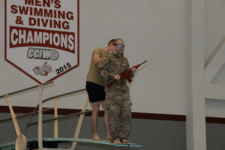 U.S. Air Force Airmen assigned to the Indiana Air National Guard, 181st Intelligence Wing, 113th Air Support Operation Squadron prepares to be pushed off of a high diving board while blind-folded to simulate an unexpected water entry during a night combat patrol at the Sports and Recreation Center on the campus of Rose-Hulman Institute of Technology in Terre Haute Feb. 6, 2016. The Airman trained on four different areas that tested different swimming methods in a combat situation. (U.S. Air National Guard photo by Senior Airman Lonnie Wiram)