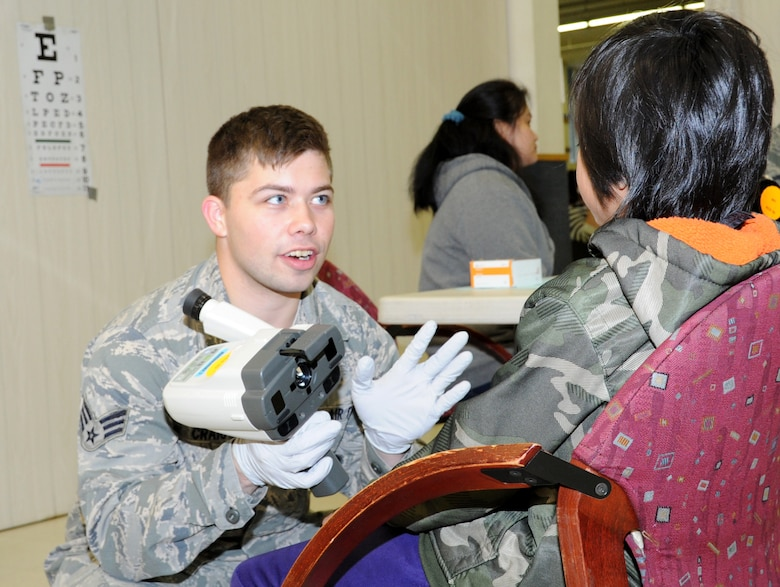 Senior Airman Jesse Craig, an ophthalmic technician assigned to the 910th Medical Squadron at Youngstown Air Reserve Station, Ohio, talks to a young patient during Arctic Care 2016 in Kodiak, Alaska. (U.S. Air Force photo by Bo Joyner)