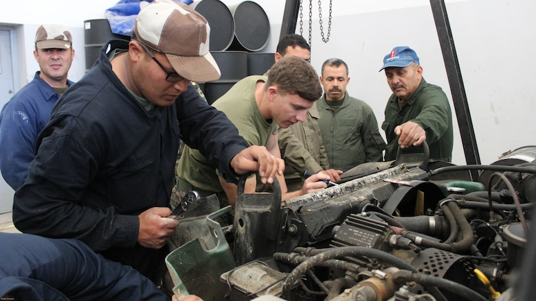 Cpl. Josh Sizelove, a motor transportation mechanic, works with Tunisian Groupement des Forces Speciales soldiers on engine parts of a HMMWV during training in Bizerte, Tunisia, Mar. 21- Apr. 8, 2016. The Marine vehicle maintenance and assistance team trained with the GFS to increase counter terrorism capabilities through motor transportation operations and maintenance training.