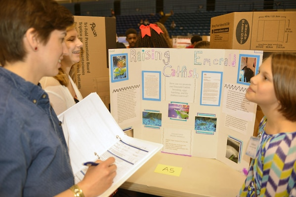 Courtney Eason, realty specialist in the Real Estate Office judges a Science, Technolgy, Engineering and Math project for students from Rucker Middle School sponsored by the Middle Tennessee STEM Innovation Hub at the Tennessee State University in 
