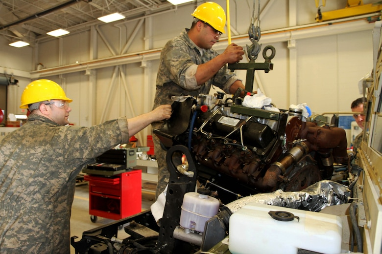 Sgt. Dana Gault (l), 978th Quartermaster Co., and Spc. Ilmer Canales, 126th Brigade Support Battalion, remove a Humvee's engine during the 80th Training Command's Wheeled Vehicle Mechanic Course at the Regional Training Site-Maintenance Fort Devens, 31 March 2016.   The three-week course teaches students the basics of how to perform maintenance and repairs on four-wheeled military vehicles, primarily focusing on Humvees and Mine-Resistant Ambush Protected vehicles.